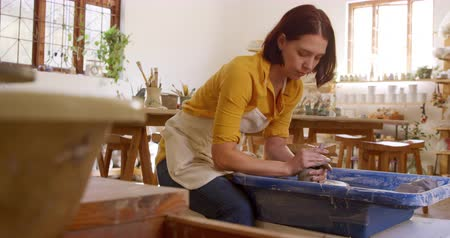bob hairstyle : Side view of a young Caucasian female potter with auburn hair in a bob hairstyle wearing an apron, sitting at a potters wheel and turning a piece of clay in a pottery studio Stock Footage