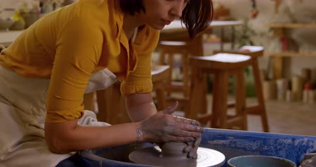 vocação : Side view close up of a young Caucasian female potter with auburn hair in a bob hairstyle sitting at a potters wheel turning a piece of clay in a pottery studio, slow motion