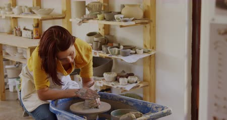 fartuch : Front view of a young Caucasian female potter with auburn hair in a bob hairstyle wearing an apron, sitting at a potters wheel, turning a piece of clay and shaping it with her hands in a pottery studio, with shelves and pots in the background