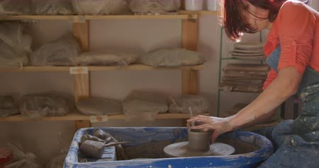 bob hairstyle : Side view of a young Caucasian female potter with auburn hair in a bob hairstyle wearing an apron, sitting at a potters wheel, turning a pot and shaping it in a pottery studio