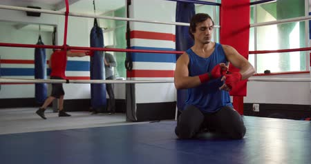 ajoelhado : Front view of a mixed race male boxer wrapping his hands with boxing bands kneeling in a boxing ring at a boxing gym, with a trainer and another male boxer training in the background, slow motion
