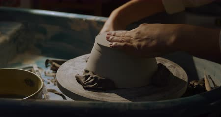 glinka : Side view mid section of a young Caucasian female potter turning a clay dish on a potters wheel and shaping it with a tool in a pottery studio