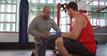 ajoelhado : Side view of a bald Caucasian male instructor kneeling and wrapping the hands of a Caucasian male boxer wearing a red vest, sitting on the side of a boxing ring, with boxing bands during a training session at a boxing gym, slow motion