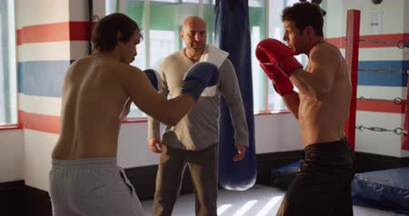 átlyukasztás : Front view of a bald Caucasian male instructor during boxing training in a boxing gym instructing two male boxers, slow motion