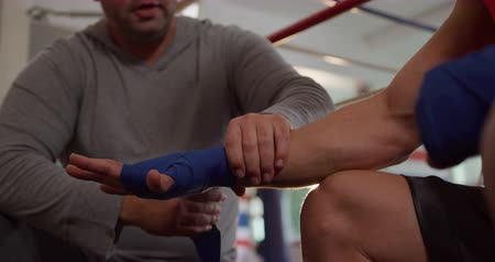 ajoelhado : Front view close up of a bald Caucasian male instructor wrapping the hands of a Caucasian male boxer with boxing bands during a training session at a boxing gym, slow motion