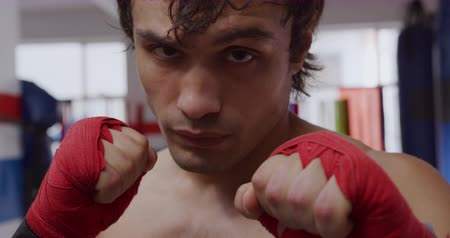 vooruitgang : Portrait close up of a young mixed race male boxer with his hands wrapped in boxing bands looking at camera in a boxing gym, slow motion Stockvideo