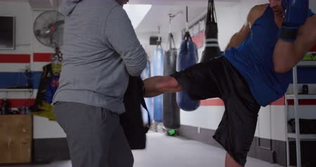 kickbox : Side view close up of a Caucasian male kickboxer practicing a kick against a pad held by a bald Caucasian male trainer in a boxing gym, slow motion
