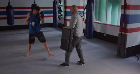 tekmeleme : Front view of a Caucasian male kickboxer practicing a kick against a pad held by a bald Caucasian male trainer in a boxing gym, slow motion Stok Video
