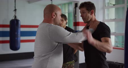 trousers : Krav Maga Training. Side view close up of a bald Caucasian male instructor giving self defence training in a boxing gym demonstrating a hold on a Caucasian man, while another man looks on, slow motion Stock Footage