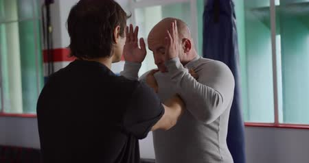 dövüş sanatları : Krav Maga Training. Front view of a bald Caucasian male instructor giving self defence training in a boxing gym to a mixed race man, slow motion