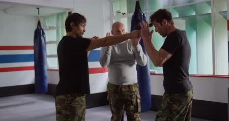 trousers : Krav Maga Training. Front view of a bald Caucasian male instructor giving self defence training in a boxing gym instructing a gun defense to a Caucasian man and a mixed race man, slow motion