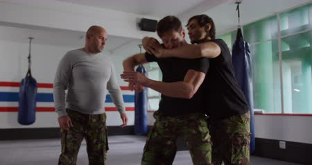 trousers : Krav Maga Training. Front view of a bald Caucasian male instructor giving self defence training in a boxing gym to a Caucasian man and a mixed race man, slow motion