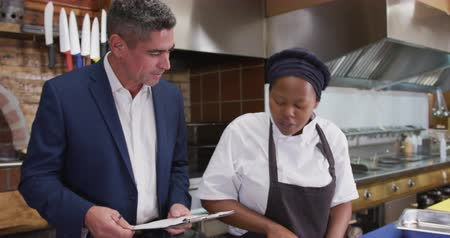 american cuisine : Front view of a Caucasian male restaurant manager in the kitchen, holding a clipboard and talking to an African American female cook, giving instructions