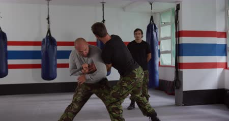 self defence : Krav Maga Training. Front view of a bald Caucasian male instructor giving self defence training in a boxing gym demonstrating a knife defense to a Caucasian man, while another man looks on, slow motion