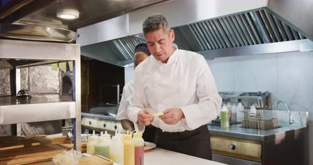 garnishing : Side view of a Caucasian male chef working in a busy restaurant kitchen, checking orders, a female African American cook garnishing food on plates ready to be served Stock Footage