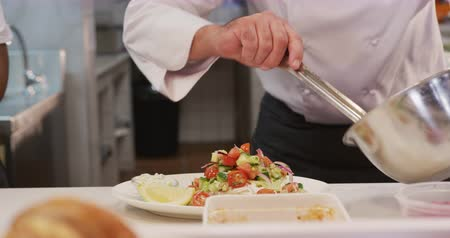 garnishing : Front view mid section of a Caucasian male chef working in a busy restaurant kitchen, garnishing plates of food ready to be served, female cook working next to him Stock Footage