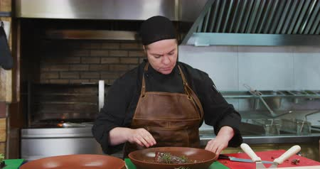 top chef : Front view of a Caucasian female cook working in a busy restaurant kitchen, garnishing and preparing steak, flames in the stove in the background