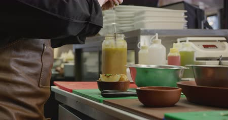 garnishing : Side view of a Caucasian female cook working in a busy restaurant kitchen, garnishing potato salad with lemon juice, her colleagues working in the background Stock Footage