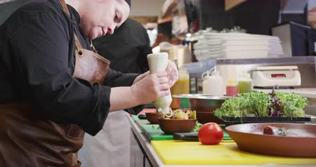 garnishing : Side view of a Caucasian female cook working in a busy restaurant kitchen, garnishing potato salad, her male colleague working in the background