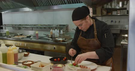 focussed : Front view of a Caucasian female cook working in a busy restaurant kitchen, placing baby tomatoes on a plate, her female colleague bringing her frying pan with food Stock Footage