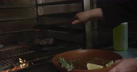tang : Close up of hands of a Caucasian female cook working in a busy restaurant kitchen, putting meat inside grill, pouring oil over flames