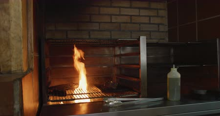 tang : Side view of a Caucasian female cook working in a busy restaurant kitchen, cooking meat inside grill, pouring oil over flames Stockvideo