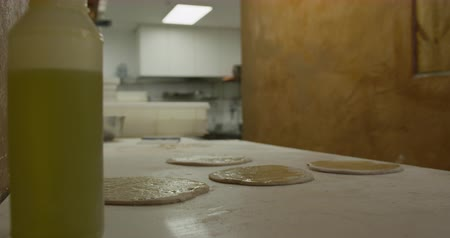 focussed : Side view mid section of an African American male cook working in a busy pizza restaurant kitchen, oiling pizza dough and putting it in the pizza oven with pizza peel Stock Footage