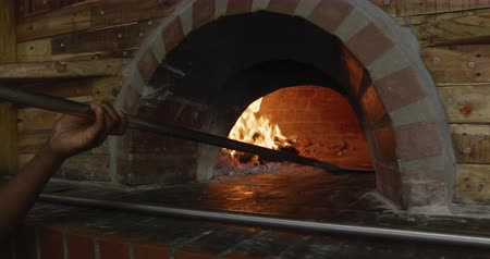 american cuisine : Side view mid section of an African American male cook working in a busy pizza restaurant kitchen, putting pizza dough in the pizza oven with pizza peel