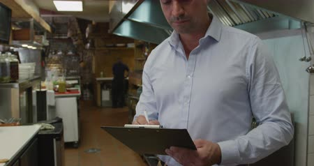 chemise à carreaux : Portrait of a happy Caucasian male manager in a busy restaurant kitchen, smiling to camera holding a clipboard and writing, cooks working in the background