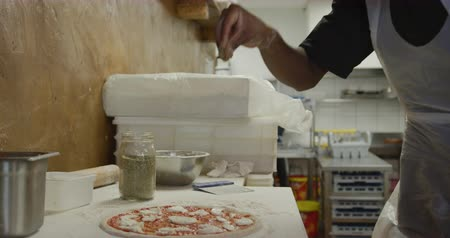 prepare food : Side view mid section of a mixed race male cook working in a busy pizza restaurant kitchen, sprinkling herbs over pizza dough before cooking Stock Footage