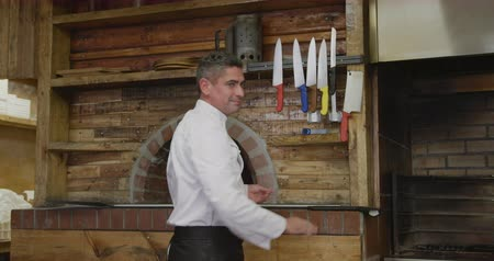 beyazlar : Portrait of a happy Caucasian male chef working in a busy pizza restaurant kitchen, putting a pizza peel on a shelf, smiling to camera and crossing his arms, pizza oven in the background