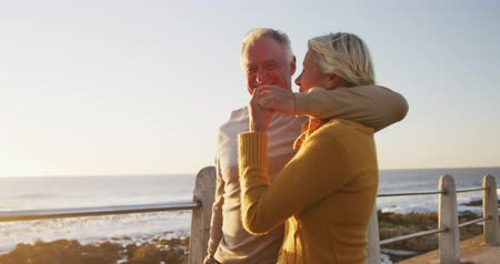 fondness : Front view of a happy senior Caucasian couple enjoying time in nature together, smiling and embracing, walking alongside beach at sunset, slow motion Stock Footage