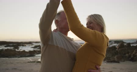 fondness : Side view of a senior Caucasian couple enjoying time in nature together, dancing on a beach at sunset, smiling, slow motion Stock Footage