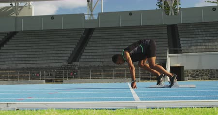 começando : Side view of a mixed race male athlete practicing at a sports stadium, starting sprinting from running blocks, slow motion Vídeos