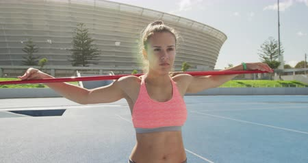 javelot : Portrait of a Caucasian female athlete at a sports stadium, holding  javelin in her arms, concentrating before competition, slow motion
