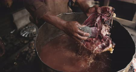 vocação : Side view mid section of an African male butcher in a township workshop, holding and washing animal head, slow motion