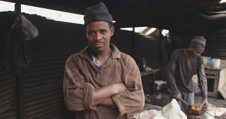 south asian food : Portrait of a happy African male butcher in a township workshop, looking at camera with his male colleague cutting fresh meat with axe in the background, slow motion