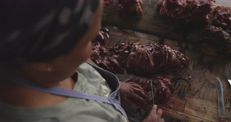 south asian food : Over the shoulder view of an African female butcher wearing a headscarf in a township workshop, cutting fresh meat with knife, slow motion Stock Footage