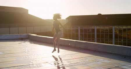 vocação : Side view of a mixed race female ballet dancer practicing on rooftop at sunrise, jumping and turning round, buildings in the background, slow motion