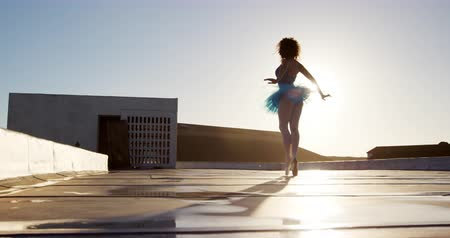 規律 : Side view of a mixed race female ballet dancer practicing on rooftop at sunrise, walking on tiptoes and turning around, slow motion