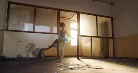 vocação : Low angle front view of a mixed race female ballet dancer practicing in an empty warehouse, jumping through a distressed doorway, slow motion
