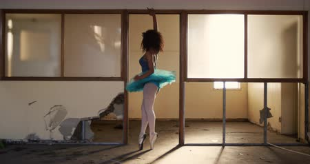 doorway : Side view of a mixed race female ballet dancer practicing in an empty warehouse, standing in a distressed doorway, turning around and stretching, slow motion Stock Footage