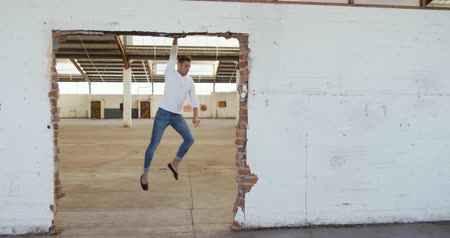 chaussures ballerines : Front view of a Caucasian male ballet dancer practicing in an empty warehouse, dancing and jumping across a distressed doorway, slow motion