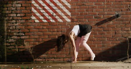規律 : Front view of a mixed race female ballet dancer practicing outside an empty warehouse, dancing and leaning against a brick wall, slow motion