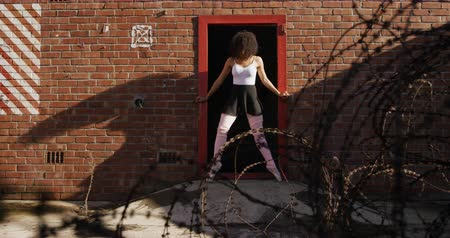 doorway : Front view of a mixed race female ballet dancer practicing outside an empty warehouse, stretching in a doorway, slow motion
