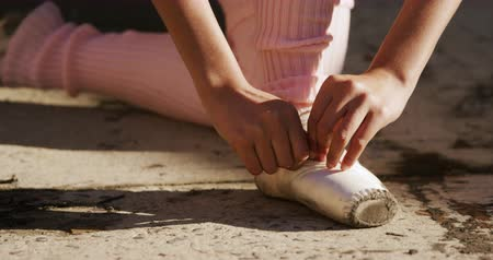 a form : Front view close up of a mixed race female ballet dancer practicing outside an empty warehouse, fastening her pointe shoes, slow motion