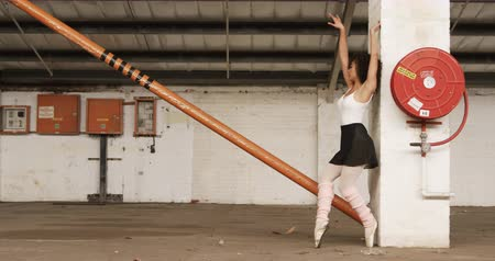 saia : Side view of a mixed race female ballet dancer practicing in an empty warehouse, dancing, turning and leaning against a pillar, slow motion Vídeos