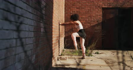 vocação : Side view of a mixed race female ballet dancer practicing outside an empty warehouse, stretching and leaning against a brick wall, slow motion Vídeos