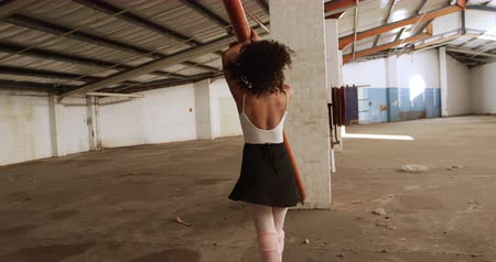 chaussures ballerines : Front view of a mixed race female ballet dancer practicing in an empty warehouse, dancing, stretching and leaning against a beam, slow motion