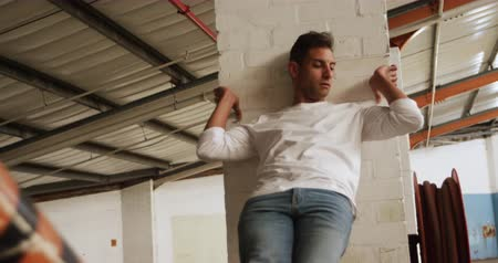 pilíře : Front view close up of a Caucasian male ballet dancer practicing in an empty warehouse, leaning against a pillar resting his legs on a beam, slow motion